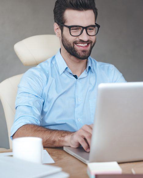 Caucasian male sitting at a laptop