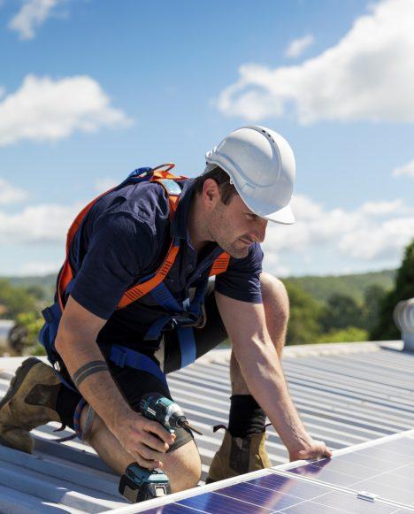 Male solar technician installing panel