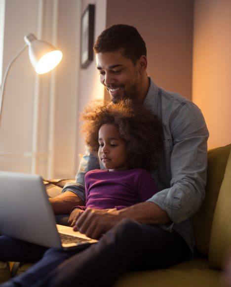 Black male with daughter on laptop