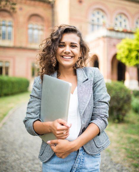 Caucasian female student holding laptop