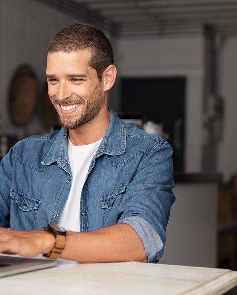 Caucasian male smiling on laptop
