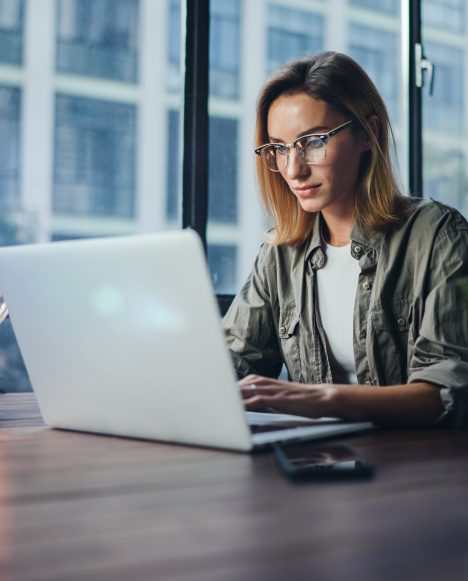Caucasian female with glasses on laptop