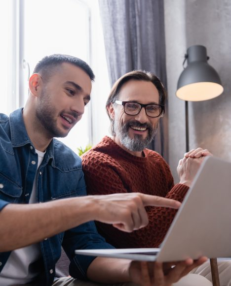 Hispanic male at laptop with father